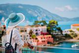 Tourist woman wearing blue sunhat and white clothes enjoying view of colorful tranquil village Assos on sunny day. Stylish female visiting Kefalonia in summer time on Greece travel vacation - 218267647