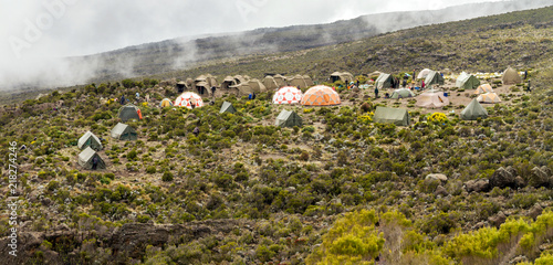 Campsite with many tents and domes on a grass and shrub hillside with mist and clouds