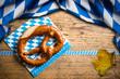Leinwanddruck Bild - Brezel mit bayrischem Tischtuch auf Holzuntergrund