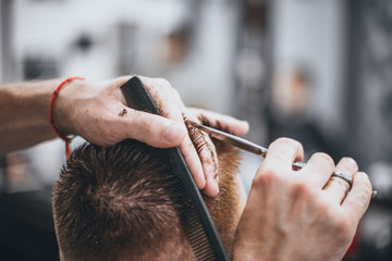 Hair Care. Barber makes a haircut with scissors. Soft focus.