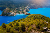 Breathtaking top view to Assos village with local houses. Landmark place of Kefalonia. Lonely white yacht at anchor in calm beautiful lagoon surrounded by pine and cypress trees. Greece - 218322842