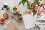 top view of delicious coffee with muffins, blank paper and alstroemeria bouquet on concrete surface