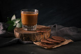 Assorted cookies in brown paper and glass of coffee with milk on dark background.