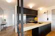 Leinwandbild Motiv Lights in black kitchen interior with bright modern countertop and wooden floor. Real photo