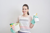 Portrait of happy woman holding in her hands cleaning products while standing at home and starting to clean. - 218363068