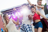Happy friends having fun at music festival - 218369227