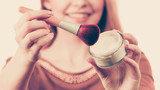 Smiling woman holding make up brush - 218370259