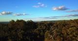 Aerial bush hilltop flyover revealing coastal plane - 218375207