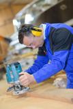 worker sanding wood for luxury yachts in boatyard - 218397698