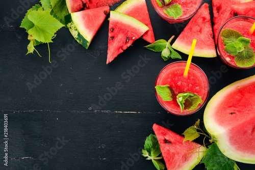 Aluminium Sap Watermelon juice with mint and ice in a glass. Melon. On a black wooden background. Free space for text. Top view.