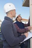 Workmen assessing drainpipe on outside of building - 218407095