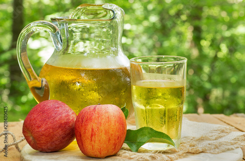 Aluminium Sap Refreshing Apple Juice With Red Apples on an Outdoor Table