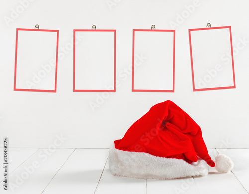 Bright red Santa Claus hat with paper frames for text or photos ...
