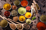 Variety of spices and herbs on kitchen table - 218465411