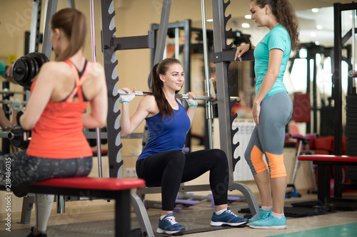 Leinwanddruck Bild Pretty young women using barbell in gym. Trainer keep watch over her