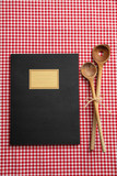 Notebook, wooden kitchen utensils on red tablecloth, top view - 218495012