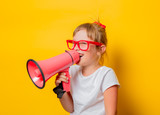 Portrait of an emotional toddler girl in glasses with megaphone on yellow background. - 218502204