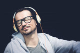 Carefree man with eyes closed listening music on headphones. - 218533865