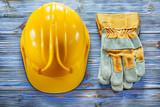 Safety gloves building helmet on vintage wooden board - 218539429