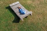 Junge in Holzliege entspannt auf Wiese - 218543433