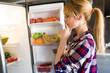 Pretty young woman hesitant to eat in front of the fridge in the kitchen.