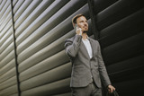 Stylish businessman walking outdoors - 218568035