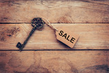 Old key with tag and text sale on wooden - 218574416