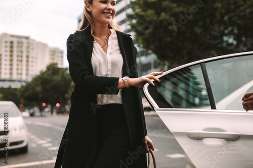Smiling woman commuter getting out of a taxi