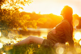 Pregnant woman sitting on green grass in summer park, enjoying nature. Healthy pregnancy concept - 218590800