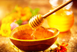 Honey dripping from honey dipper in wooden bowl. Healthy organic thick honey pouring from the wooden honey spoon closeup - 218590833