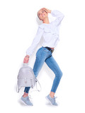 Beauty fashion model girl dressed in jeans and sneakers, holding trendy silver backpack and posing in studio, isolated on white background. Beautiful woman in urban outfit, fashion wear - 218591087