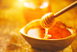 Honey dripping from honey dipper in wooden bowl. Healthy organic thick honey pouring from the wooden honey spoon closeup - 218592615