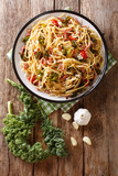 Italian food: pasta linguine with fried bacon, vegetables and parmesan cheese close-up on a plate. Vertical top view