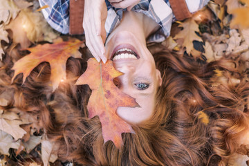 young red hair beauty lying in orange autumn leafes