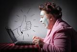 femme drôle avec bigoudis surfant son ordinateur portable avec dessin de pouce levé - 218657036