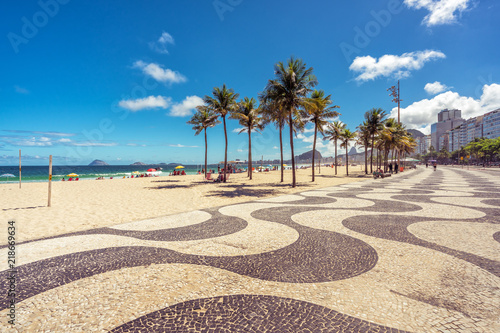 Copacabana Beach with palms and famous mosaic sidewalk in Rio de Janeiro, Brazil.