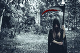 Female demon witch with bloody reaper standing in front of mystery forest background. Halloween and Religious concept. Demon angel and Satan theme. - 218671222