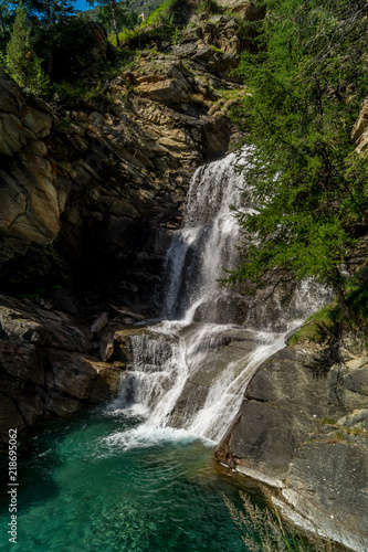 waterfall in the mountains among the rocks - 218695062