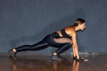 athletic sportswoman stretching legs indoors, gym © Schum