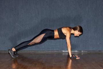 muscular fit woman doing plank in gym dark interior © Schum