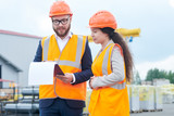 Waist up portrait of successful bearded businessman wearing hardhat and holding clipboard talking to female factory employee outdoors - 218713285