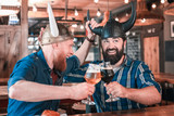 Thematic pub. Two funny mature men wearing Vikings hats feeling relieved while sitting in thematic pub - 218730648