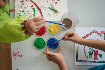 Young children painting with colourful acrylics © Gajus