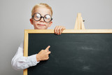 Kind als Schüler zeigt auf Schultafel - 218741250