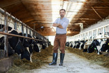 Young man with his arms crossed on ches standing by stable of dairy cows in kettlefarm