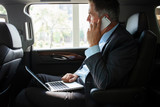 Handsome businessman talking with phone sitting with laptop on the backseat of the car. - 218745214