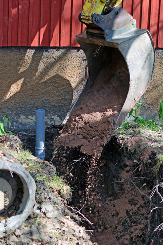 Excavator in construction site filling the sewer pipe trench with