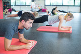 fit men and women doing push-ups at fitness club