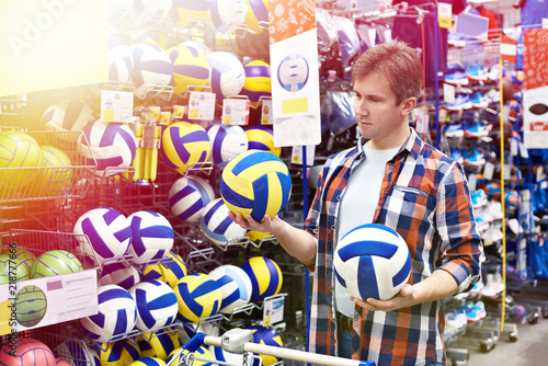 Fototapeta Man chooses volleyball in sports shop