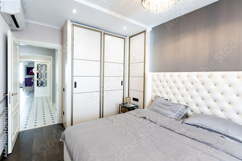 Modern bedroom interior with a big bed and a Chandelier